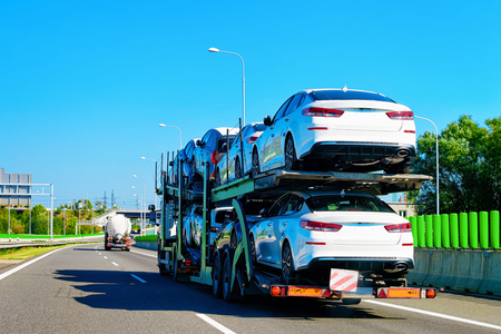 Cars carrier truck at the asphalt road of Poland. Truck transporter Stock Photo