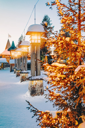 Street lantern in Santa Claus Village with Christmas trees at dusk, Lapland. Finland, on Arctic Circle in winter.