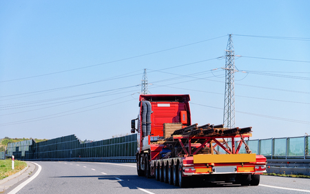 Red Truck in the highway road in Slovenia. Lorry transport delivering some freight cargo.