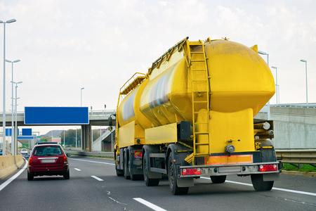 Yellow Tanker storage truck on the asphalt highway, Poland. Business industrial concept.