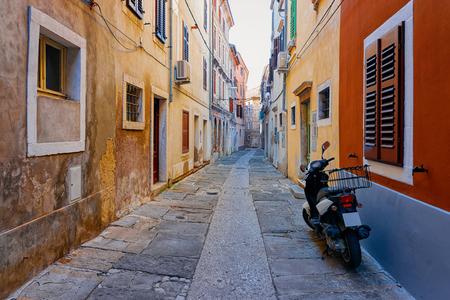 Motorfiets in de oude straat van het historische stadscentrum van Izola, Slovenië Stockfoto