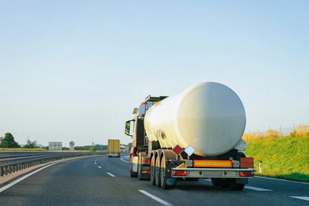 White Tanker storage truck at the asphalt highway, Poland. Business industrial concept.