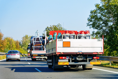 Truck carrying cisterns in the highway road in Slovenia. Lorry transport delivering some freight cargo. Banque d'images