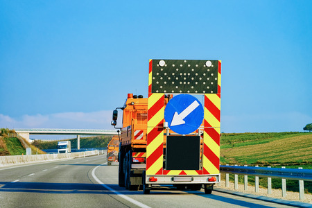 Truck carrying arrow down left reflective road sign in highway in Poland.