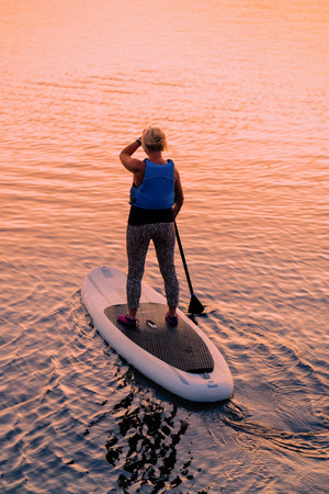 Woman standing up on Paddle boat on Galve Lake in Trakai in Lithuania. At sunset Reklamní fotografie