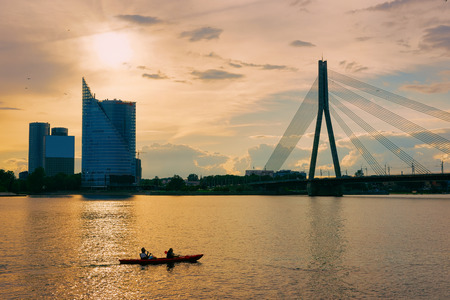 People in canoe on Daugava River and business downtown with Vansu Bridge in Riga in Latvia. Фото со стока
