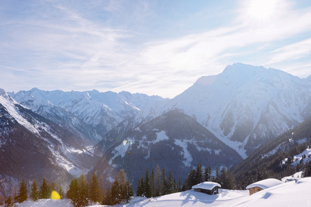 Landscape of Penken ski resort and snowy chalet in Zillertal in Tyrol. Mayrhofen in Austria in winter in Alps. Alpine mountains with snow. Blue sky and white slopes at Zell am Ziller.