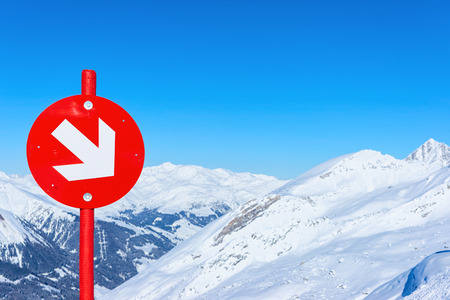 Red direction sign at Hintertux Glacier ski resort in Zillertal in Tyrol in Austria, winter in Alps. Alpine mountains with snow. Downhill fun. Family vacation. Blue sky and white slopes.