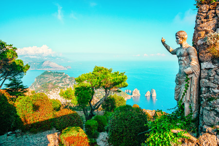 Statue and gardens in Capri Island town in Italy at Naples. Landscape with Blue Mediterranean Sea at Italian coast. Anacapri in Europe. View on Faraglioni in summer. Amalfi scenery and Solaro mountain Imagens