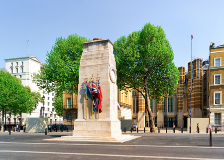 Cenotaph War Memorial with flags on Whitehall on downtown street in London in the UK. Square with green trees in England, British capital of United Kingdom. Cityscape in daytime in spring.