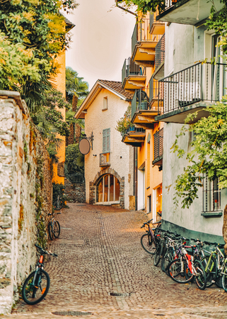 Cobblestoned Street with bicycles at romantic luxury resort in Ascona town on Lake Maggiore of Ticino canton in Switzerland. Outdoor expensive family travel in Swiss city in summer. Italian Holiday