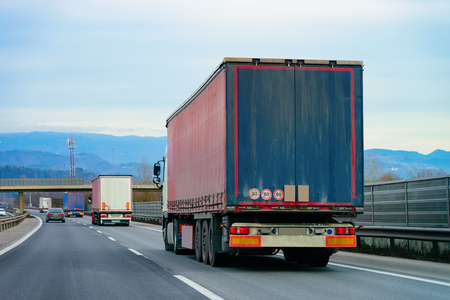 Trucks in road. Trucker in highway. Lorry doing logistics work. Semi trailer with driver. Big cargo car. Freight delivery. Transport export industry. Container with loaded goods on background.