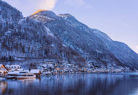 Hallstatt near Salzburg in Austria, Europe, in evening. Winter in Salzkammergut. Travel to Austrian city with lake at Christmas. Alpine Land with snow. View on Village near Alps mountains