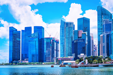 Skyline of Downtown Core at the Marina Bay Financial Center in Singapore. With Merlion statue. Редакционное