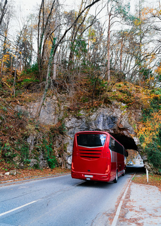 Red bus on the road at the tunnel in the mountains in Bled in Slovenia. Travel in Europe