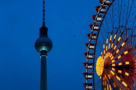 Ferris wheel and Fernsehturm at Christmas market at Germany in Europe in winter. German street Xmas holiday fair in Berlin at Berliner Rathaus. An night