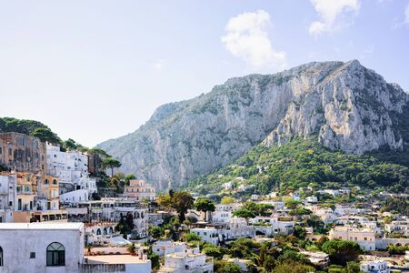Cityscape with house architecture at Capri Island at Naples in Italy. Landscape at Blue Mediterranean Sea at Italian coast. Anacapri in Europe. View in summer. Amalfi scenery and Solaro mountain