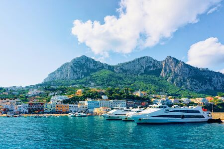 Marina with yachts in Capri Island town at Naples in Italy. Landscape with Blue Mediterranean Sea at Italian coast. Anacapri in Europe. View on Faraglioni in summer. Amalfi scenery and Solaro mountain