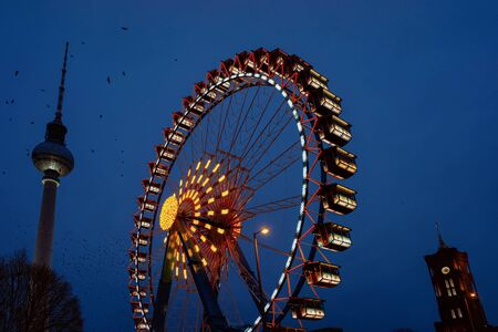 Ferris wheel and Fernsehturm on Christmas market at Germany in Europe in winter. German street Xmas holiday fair in Berlin at Berliner Rathaus. An night