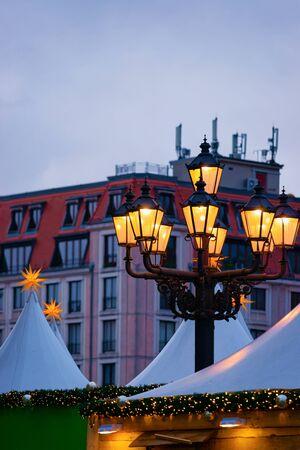 Street lanterns at Evening Christmas market in Gendarmenmarkt in Berlin in Germany in Europe in winter. Lamps at German Night street Xmas and holiday fair in European city in December.