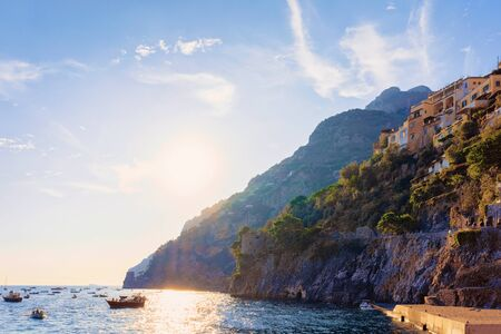 Citiscape and landscape with sunset and boats at Positano town on Amalfi Coast and Tyrrhenian Sea in Italy in summer. View of beautiful Mediterranean architecture near Sorrento. Europe travel