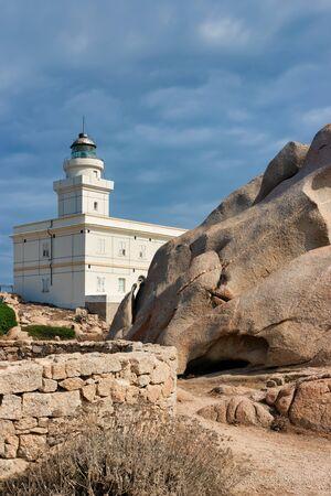 Lighthouse in Capo Testa in Santa Teresa Gallura province on Sardinia island in Italy. At the Mediterranean sea with Rocky mountains.