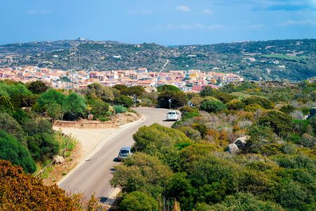 Cars with driving in the highway road at Capo Testa in Santa Teresa Gallura at the Mediterranean Sea on Sardinia Island in Summer Italy. Holiday adventure in mountains. Stock Photo