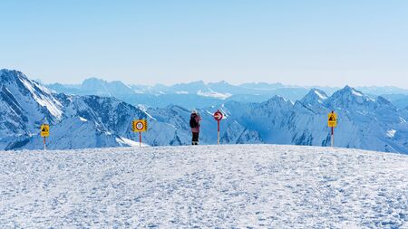 Woman with digital camera taking photos in Hintertux Glacier ski resort in Zillertal in Tyrol in Austria in winter in Alps. Alpine mountains with snow. Lady and Blue sky and white slopes.
