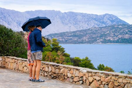 Coppia con ombrellone in un giorno di pioggia all'isola di Tavolara a Capo Coda Covallo, San Teodoro nel Mar Mediterraneo in provincia di Olbia-Tempio, Sardegna, Italia Archivio Fotografico