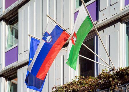 Slovenian flag, Ljubljana flag and EU flag on building in Ljubljana old town streets, Slovenia in evening. Slovenian city view in spring. Landmark. Urban green capital.