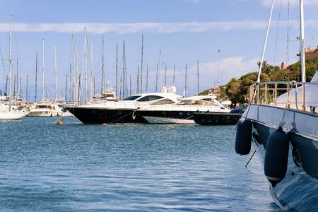 Marina with luxury yachts in Mediterranean Sea at Porto Cervo in Sardinia Island in Italy in summer. View on Sardinian town port with ships and boats in Sardegna. Zdjęcie Seryjne