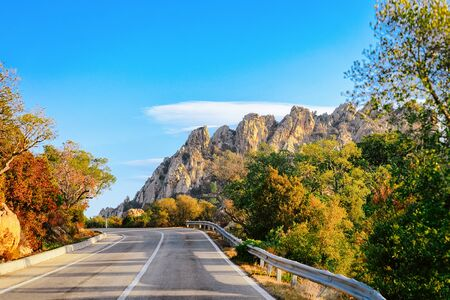 Empty road without cars, in Sardinia Island in Italy in summer. Panorama with highway and green nature and blue sky. Mountains on the background.