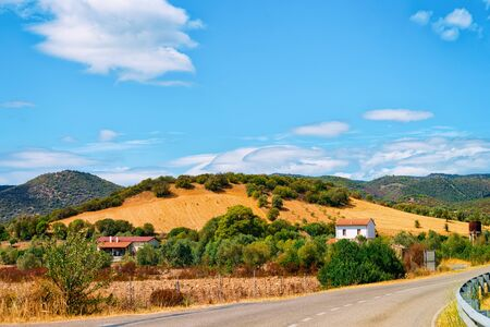 Scenery with highway at Carbonia near Cagliari in Sardinia in Italy. View with nature in the road. Mountains and hills and Mediterranean sea on the background. Blue sky and white clouds.