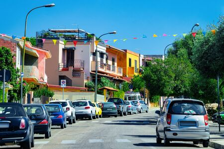 Street view with cars parked in the Road in town in province of Cagliari in Sardinia Island in Italy. Cityscape with building architecture.