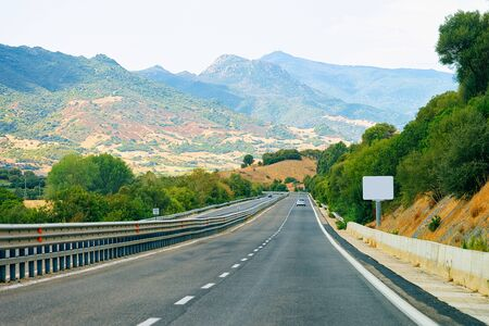 Empty road without cars on Sardinia Island in Italy in summer. Panorama with highway and green nature and blue sky. Mountains on the background.
