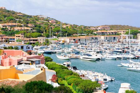 Marina with luxury yachts at Mediterranean Sea in Porto Cervo in Sardinia Island in Italy in summer. View on Sardinian town port with ships and boats in Sardegna.