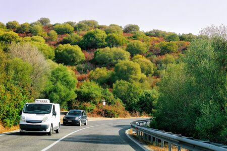 Rv cavaran and car on the road in Costa Smeralda on Sardinia Island in Italy in summer. Motorhome rving on motorway. Camper trailer on highway.