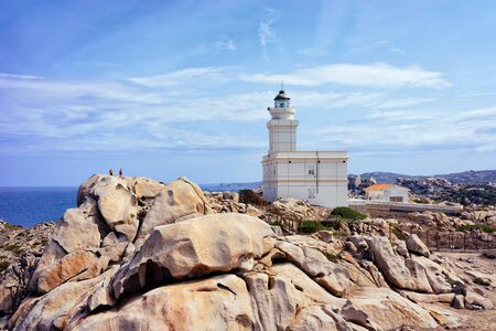 Lighthouse at Capo Testa in Santa Teresa Gallura province on Sardinia island in Italy. At the Mediterranean sea with Rocky mountains.