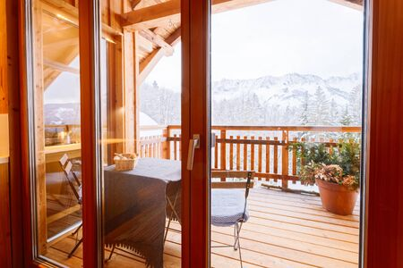 View from Balcony of living room on Austrian Alps mountain in snow winter. Design of modern apartment house with open terrace and Alpine scenery in Austria. Decor. Stylish lifestyle. Table with chairs
