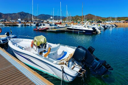 Old Sardinian Marina with ships near Mediterranean Sea in city of Villasimius in South Sardinia Island in Italy in summer. Cityscape with port and Yachts and boats Zdjęcie Seryjne