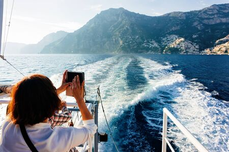 Tourist taking photos on camera during cruise excursion tour on boat in Tyrrhenian Sea in Positano town of Amalfi Coast, Italy, summer. Beautiful Mediterranean view near Sorrento. Travel and tourism Stock fotó