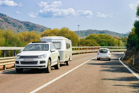 Rv cavaran and car in the road in Costa Smeralda on Sardinia Island in Italy in summer. Motorhome rving on motorway. Camper trailer on highway.