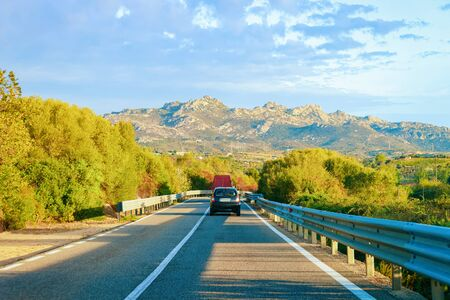 Cars at the road in Costa Smeralda in Sardinia Island in Italy in summer. Transport driving on the highway in Europe. View on motorway.