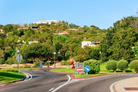 Empty road without cars at Porto Cervo luxury resort in Sardinia Island in Italy in summer. Panorama with highway and green nature and blue sky.