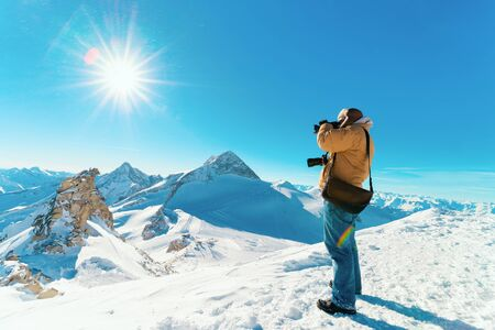 Man with digital camera taking photos in Hintertux Glacier ski resort in Zillertal in Tyrol in Austria in winter in Alps. Alpine mountains with snow. Person and Blue sky and white slopes.