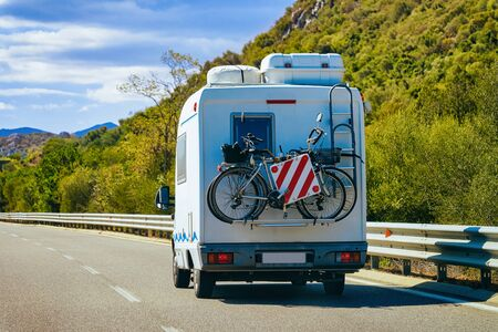 Rv cavaran with bicycles on the road in Costa Smeralda on Sardinia Island in Italy in summer. Motorhome rving and bikes on motorway. Camper trailer and wheels on highway.