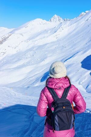 Woman with backpack in Hintertux Glacier ski resort in Zillertal in Tyrol in Austria in winter in Alps. Alpine mountains with snow. Lady and Blue sky and white slopes.