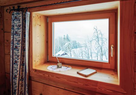 Window with view of Alpine mountains in snowy winter in Austria. Window and snowy Alps. Interior of contemporary living room of modern apartment house. Home and landscape. Deocr. Rustic, vintage style