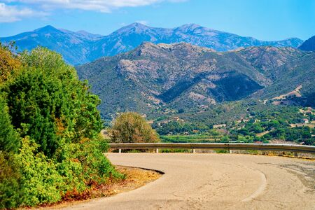 Empty road without cars in Sardinia Island in Italy in summer. Panorama with highway and green nature and blue sky. Mountains on the background.