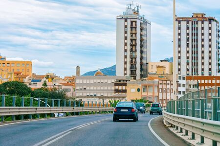 Cars on summer road in Olbia city on Sardinia Island in Italy. Ride on Driveway. Italian journey. Cityscape with architecture.